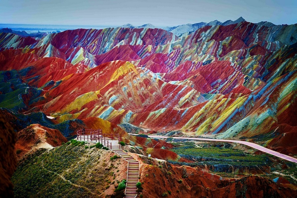 A visitor stands at a viewing platform in the Zhangye Danxia Landform Geological Park in Zhangye, northwest Chinas Gansu province. The Danxia (red rays of the sun) landform is a unique type of petrographic geomorphology which is found only in China, consists of red-colored sandstones and conglomerates of largely Cretaceous age. The unusual colours of the rocks are the result of red sandstone and mineral deposits being laid down over 24 million years. The resulting layer cake was then buckled by the same tectonic plates responsible for parts of the Himalayan mountains. Wind and rain finished the job by carving weird and wonderful shapes including natural pillars, towers, ravines, valleys and waterfalls - that differ in colour, texture, shape, size and pattern. The area is fast becoming a popular tourist attraction for the sleepy town of Zhangye. A number of boardwalks and roads have been built to encourage visitors to explore the amazing rock formations.